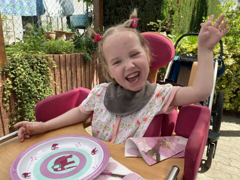 Ein lachendes Mädchen am Esstisch im Garten.