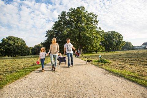 Eine Familie macht einen Spaziergang in grüner Umgebung.