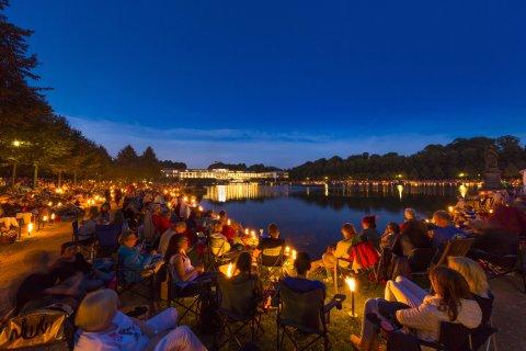 Viele Menschen sitzen um den Hollersee und genießen ein klassisches Konzert