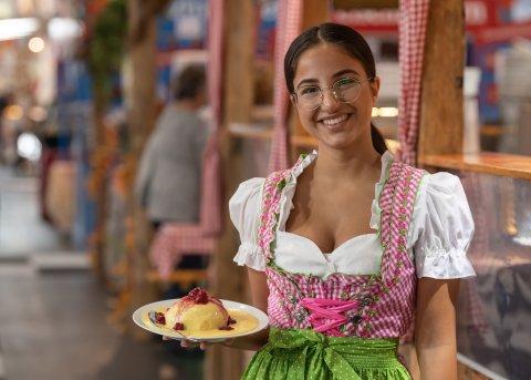 Eine junge Frau im Kleid hat einen Teller mit Essen in der Hand und grinst in die Kamera.