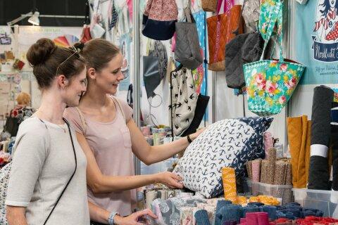 Zwei Frauen schauen sich bunte Taschen an einem Stand an.