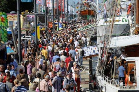 Rechts stehen viele Schiffe am Steg. Auf der linken Seite stehen und laufen viele Menschen.