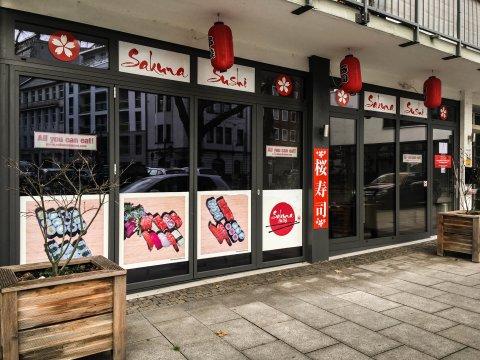 Das Sushi-Restaurant Sakura von außen. Es stehen Blumenkübel dafür. Rote Laternen hängen von der Decke.