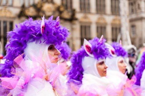 Mehrere Personen beim Bremer Samba Karneval. Drei Frauen haben Ein weißes Kostüm an, auf dem Kopf haben sie lila Federn und weiß-pinke Ohren. Sie sind bunt geschminkt.
