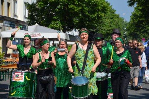 Eine Gruppe von Frauen in grünen Kostümen spielt Trommeln.