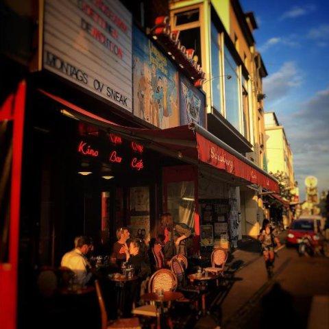 Die Schauburg mit Menschen an Tischen vor der Tür in der Abendsonne