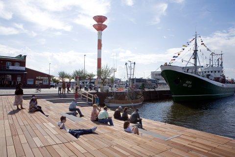 Schaufenster Fischereihafen in Bremerhaven: Menschen sitzen entspannt am Wasser.