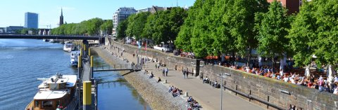 Die Weserpromenade Schlachte mit zahlreichen Fußgängern und Gastronomiebetrieben. An den Anlegern liegen kleinere Schiffe.