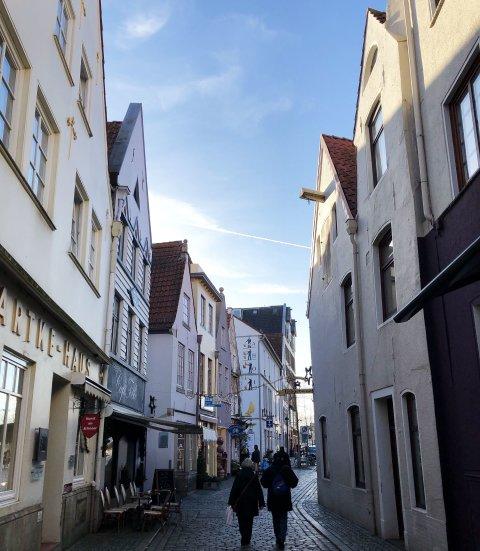 Eine schmale Gasse zu deren Seiten alte Fachwerkhäuser stehen. Zwei Personen laufen die Gasse entlang, in der sich verschiedene Geschäfte, wie zum Beispiel ein Café, befinden.