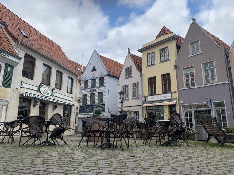 Bunte Häuser reihen sich um einen kleinen Platz im Bremer Schnoorviertel. Auf dem Platz selbst stehen Tische sowie hochgeklappte Stühle.