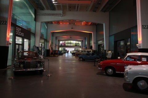 Schuppen Eins in der Überseestadt: Eine hohe Halle durch die ein breiter Gang führt, dieser ist von älteren Autos umgeben und dahinter liegen die Geschäfte.
