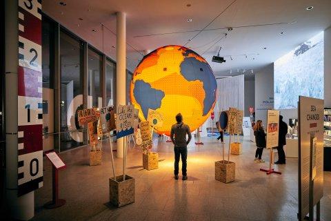 Ein Mann steht vor einer großen leuchtenden Weltkugel. Um ihn herum sind Demonstration Schilder mit klimapolitischen Sprüchen aufgestellt.