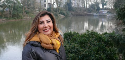 Senaa Al Khaffaji lächelt in die Kamera. Sie steht in den Wallanlagen.