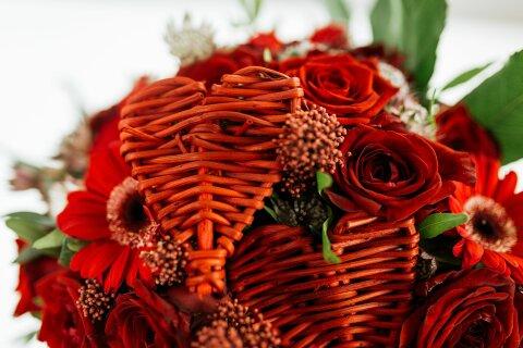 Zwischen roten Rosen stecken kleine Holzherzen.