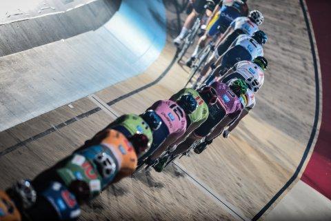 Zahlreiche Radrennfahrer fahren in einer Reihe hintereinander her.