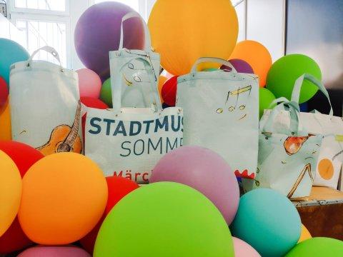 Sechs Taschen, die aus den Bannern des Stadtmusikantensommers kreiert wurden, werden vor vielen, bunten Luftballons präsentiert.