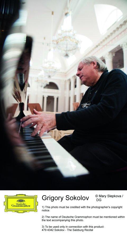 Grigory Sokolov sitzt an seinem Flügel. Er ist komplett in schwarz gekleidet