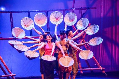 Auf einer Bühne stehen Schauspieler in einem Kreis, und haben Strohhüte in der Hand.