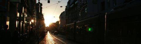 Die Sonne steht tief über dem Steintor mit Passanten und Straßenbahn.
