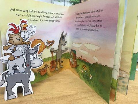 Pappfigur der Bremer Stadtmusikanten vor einem aufgeschlagenen Bilderbuch