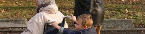 Eine Seniorin sitzt im Rollstuhl und wird von einem Kind geschoben (Quelle: fotolia / silonos).