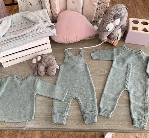 Die Aufnahme zeigt einen Pullover, eine Latzhose sowie einen Strampler für Babies. Zudem ist ein Kissen in Herzform sowie ein kleiner Stoff-Elefant zu sehen.