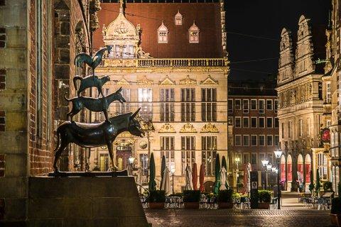 Blick auf die Bremer Stadtmusikanten bei Nacht vor dem Hintergrund des beleuchteten Marktplatzes mit dem Schütting.