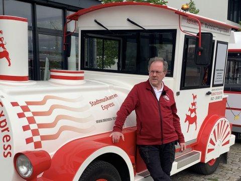 Der rot-weiße Stadtmusikanten-Express im Stil einer Lokomotive. Der Fahrer des Gefährtes steht vor dem Stadtmusikanten-Express.