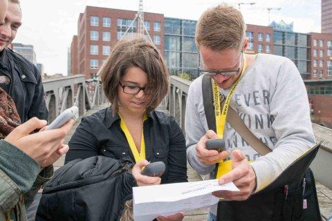 Mehrere Personen schauen auf einen Zettel und halten digitale Geräte in die Luft