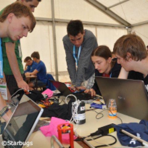 Junge Menschen arbeiten an einem Minisatelliten.