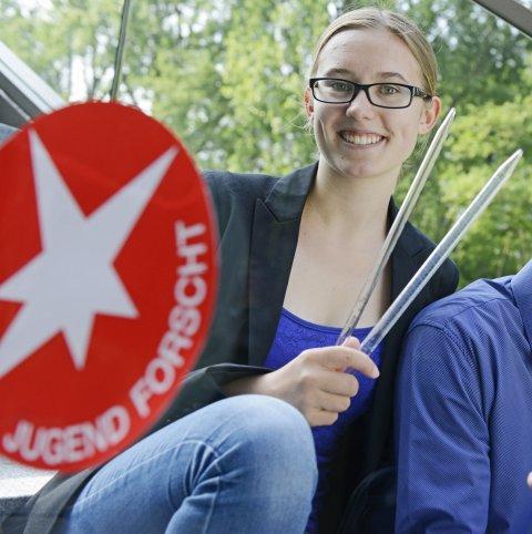 Ein junger Mann und eine junge Frau mit Forschungsgeräten neben dem Jugend forscht Logo