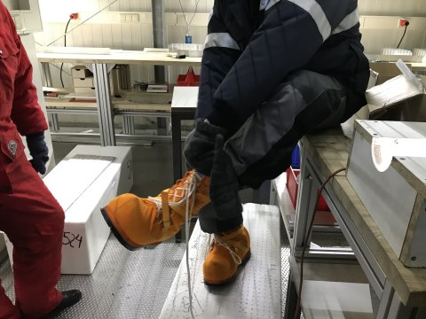 Ein Mann mit dicken gelben Schuhen und Winterbekleidung in einem Labor