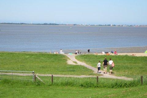 Grüne Wiese, im Hintergund Menschen am Strand.