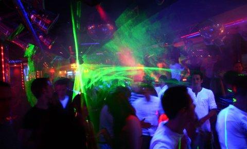 Tanzende Menschen werden von grünen Lasern angestrahlt.