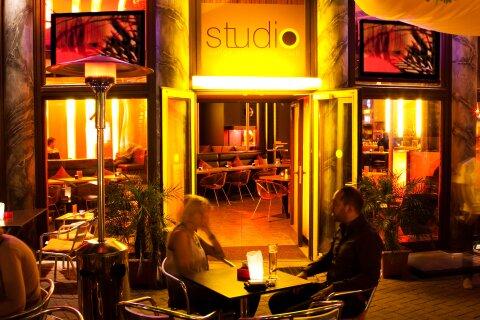 Zwei Menschen sitzen vor einer Bar und trinken etwas.