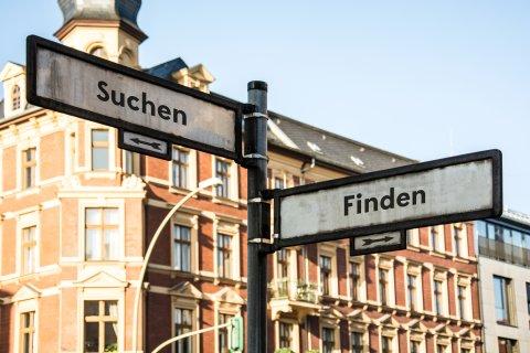 Ein Straßenschild zeigt nach links mit der Aufschrift Suchen und ein weiteres nach rechts mit der Aufschrift Finden. Im Hintergrund steht ein rotes Altbauhaus.
