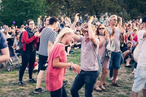 Viele junge Leute tanzen auf der Hügelbühne beim Open-Air-Festival-Summersounds