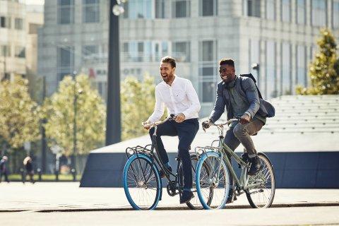Zwei Männer fahren mit ihrem Swapfiets Fahrrad zur Arbeit