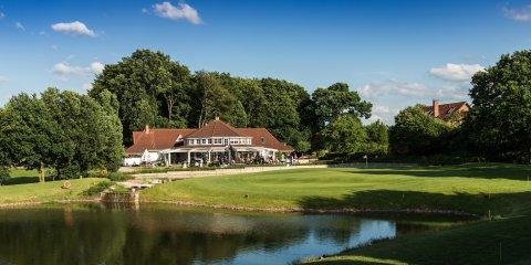 Zu sehen ist das Clubhaus der Golfanlage Syke direkt am Wasserloch.