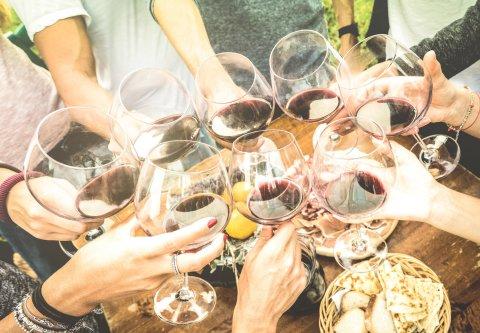 Freunde stoßen mit Rotwein an einem gedeckten Tisch an