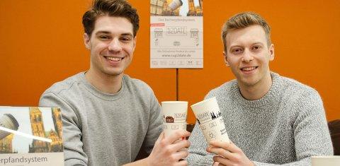 Ein Teamfoto mit den beiden Jungs von Cup2date, die Pfandbecher in der Hand halten.