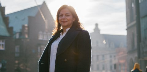 Eine junge Frau steht in der Bremer Innenstadt und blickt in die Kamera. Hinter ihr geht die Sonne auf und man blickt in Richtung Domsheide.