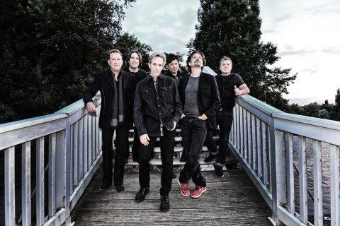 Zu sehen sind die sechs Mitglieder der Band The Hooters. Sie stehen draußen auf einer Treppe aus Holz und gucken in die Kamera.