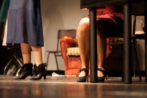 Die Füße zweier Schauspielerinnen inmitten der Kulisse auf einer Bühne im Theater