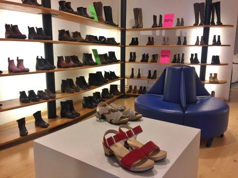 Schuhregale an den Wänden und zwei Paar Sandalen im Vordergrund.