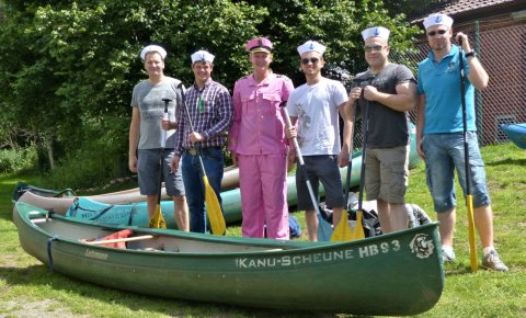 Sechs Männer mit Matrosen-Mütze, einer ganz in Pink gekleidet, stehen mit Paddeln zwischen einigen Paddelbooten der Kanu-Scheune.