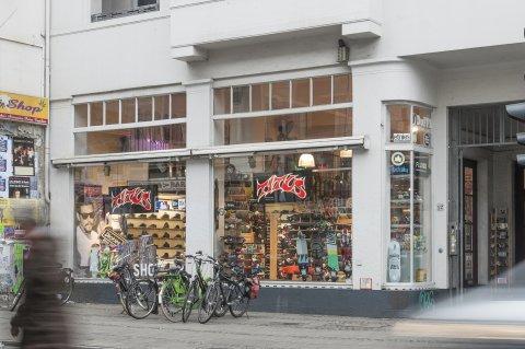 Der Laden Titus von außen. Es sind Schuhe und Skateboards im Fenster zu sehen. Vor dem Geschäft stehen mehrere Fahrräder und es geht eine Person vorbei.