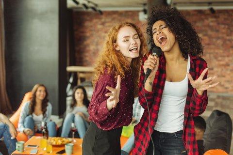 Zwei Frauen singen zusammen in ein Mikrofon.