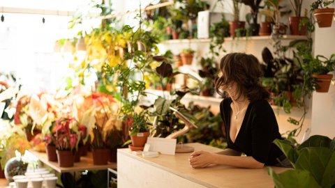 Inhaberin Nina lehnt am Tresen und blickt nach draußen. Um sie herum stehen verschiedene Pflanzen.
