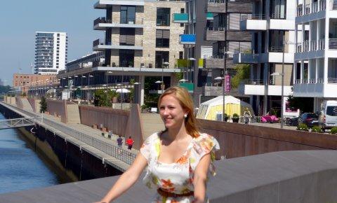 Eine Dame fährt vor Neubauten Fahrrad